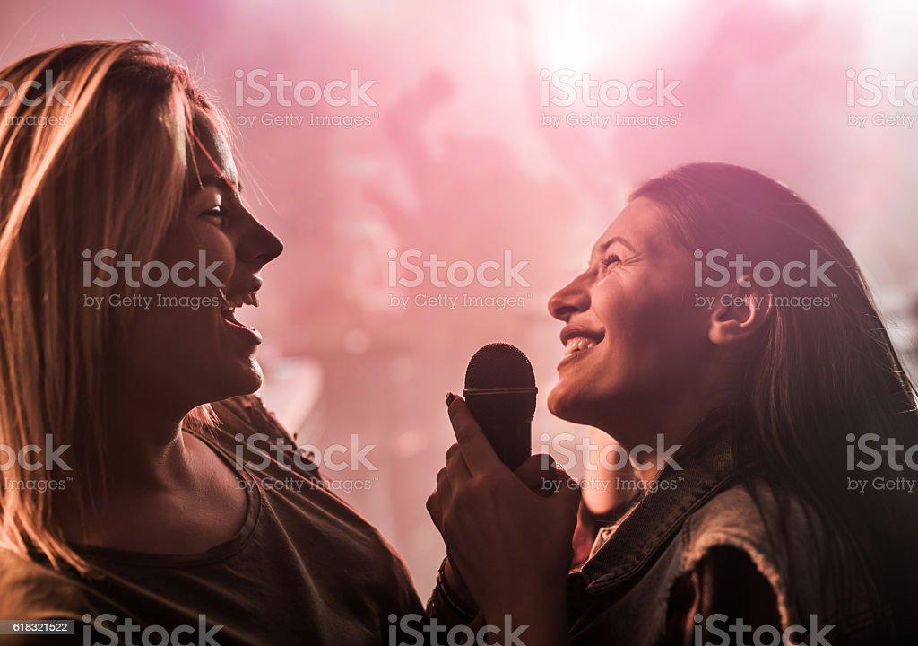Two cheerful women singing karaoke at disco club. stock photo