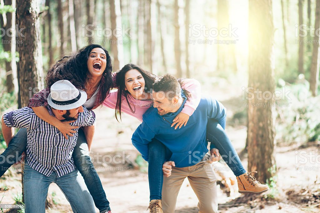 Two cheerful young couples in piggyback at the sunny forest royalty-free stock photo
