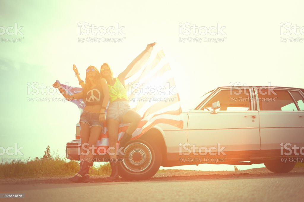 Two cheerful young hipster women wrapped in american flag stock photo