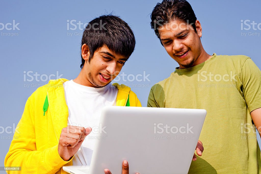 Two Cheerful Young Indian Adult Youth Standing Laptop Outdoor Horizontal royalty-free stock photo