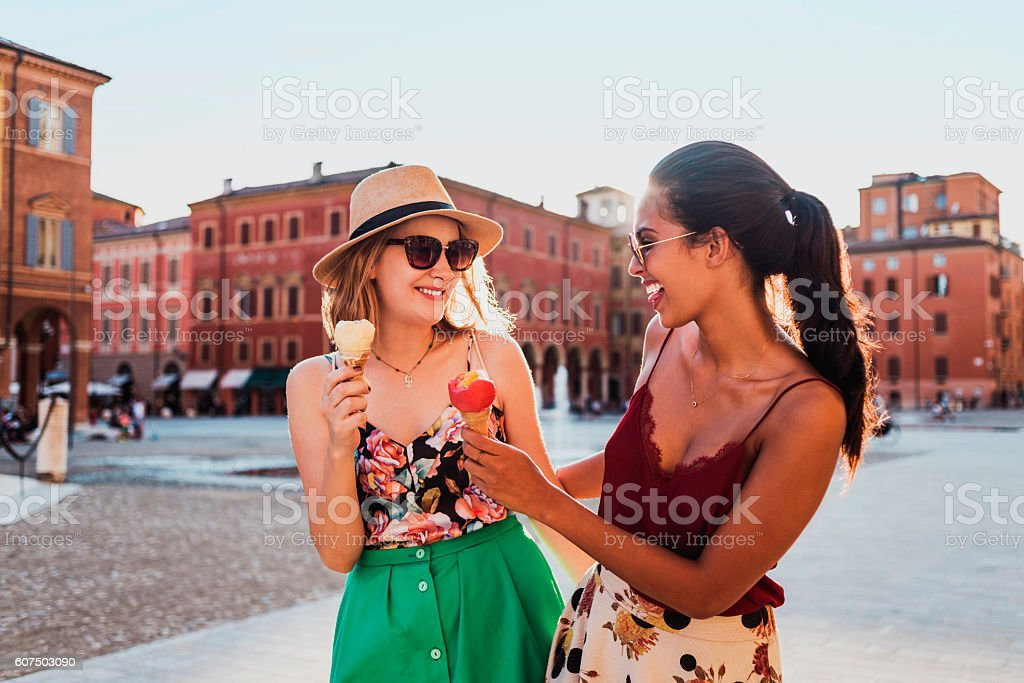 two cheerful young women eating ice cream and having fun stock photo