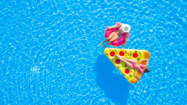 AERIAL duas alegres jovens desfrutando na boia inflável conversando na piscina - foto de acervo