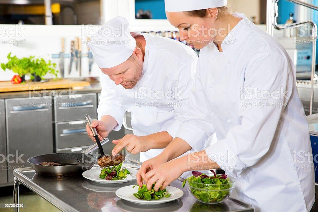 Deux nos chefs préparent un plat de viande au restaurant gastronomique - Photo