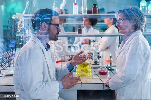 499203366istockphoto Two chemists talking about scientific research in the laboratory. 944275440