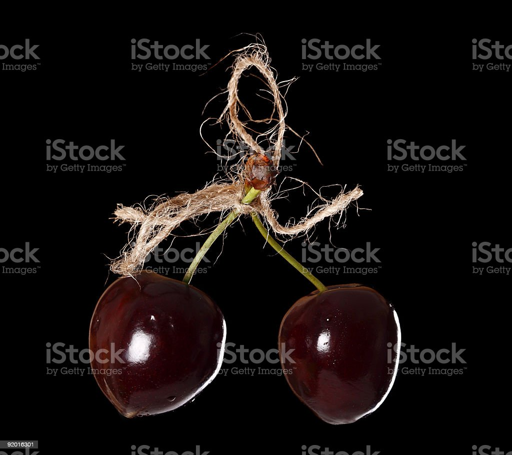two cherryes tied by rope over black background royalty-free stock photo