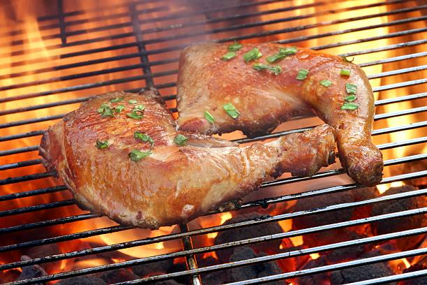 Two Chicken Quarter On The Hot BBQ Grill Close-up. Two Glazed Chicken Quarter On The Hot BBQ Charcoal Flaming Grill Close-up. drumstick stock pictures, royalty-free photos & images