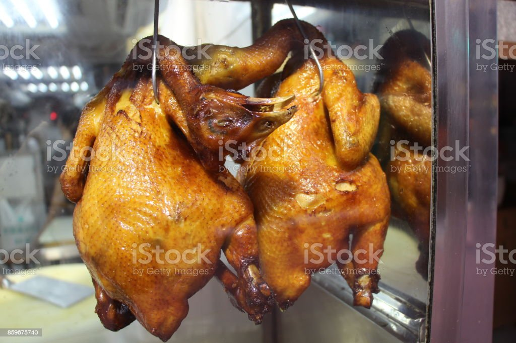 Two chickens roasted in Chinese style hang off hooks stock photo