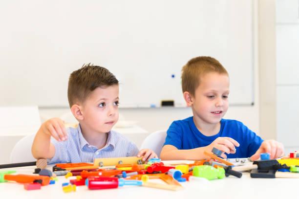 zwei kinder spielen reparatur gespielen - kindergarten handwerk stock-fotos und bilder