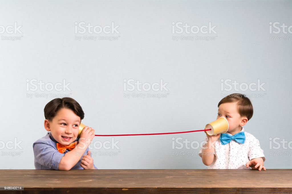 Two childeren are using paper cups as a telephone stock photo