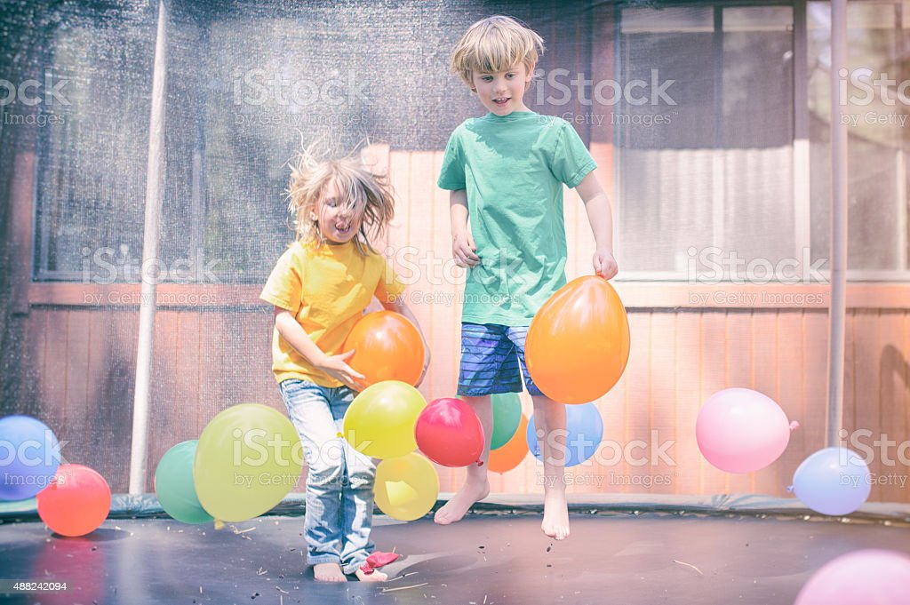 Two children bounce on a trampoline surrounded by balloons stock photo