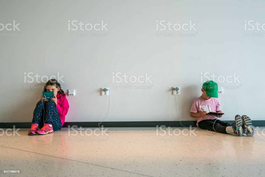 Two children, boy and girl sitting on a floor concentrating and playing electronic games. stock photo