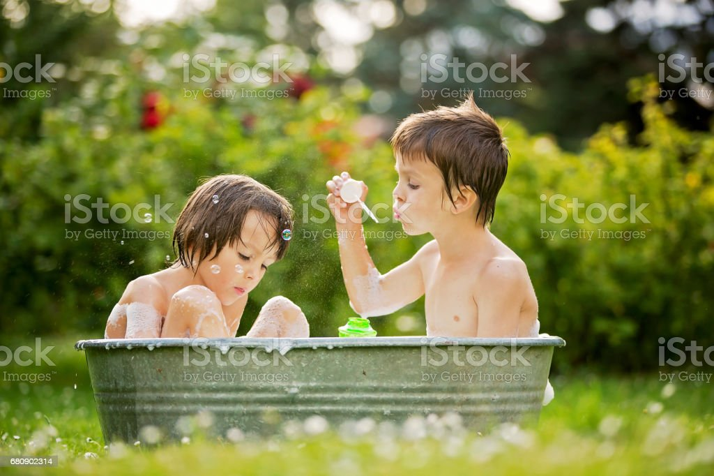 Two children, boy brothers, having a bath outdoors, making soap bubbles, summertime royalty-free stock photo