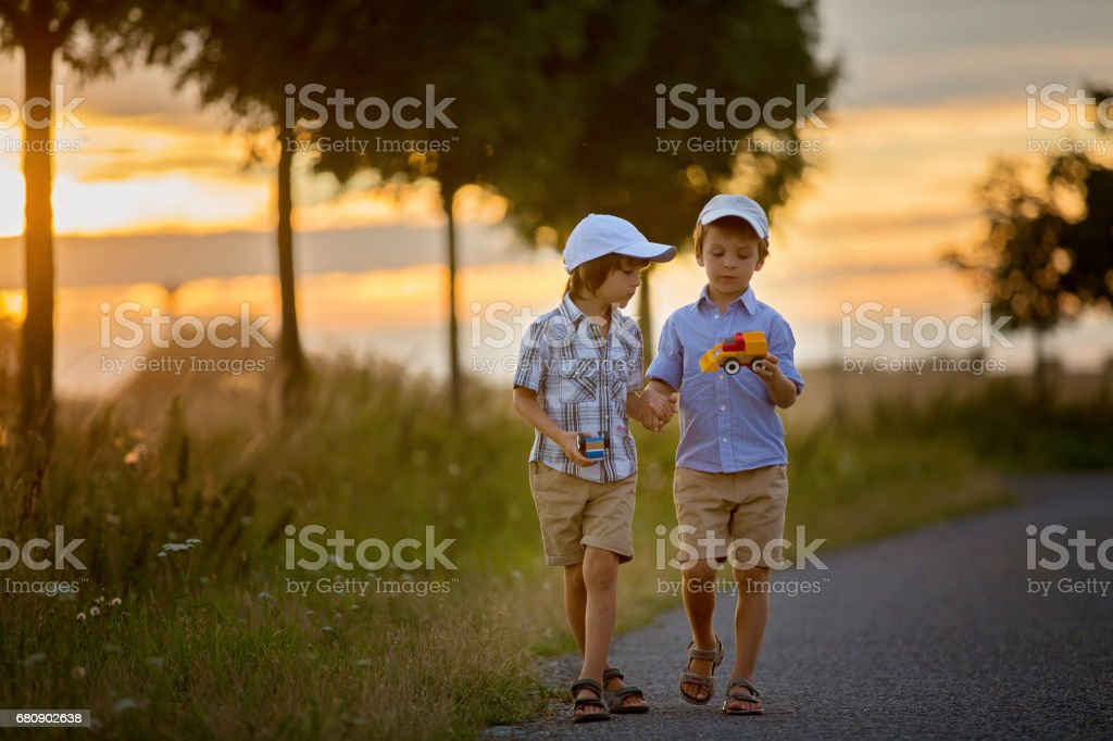 Two children, boy brothers, having fun outdoors with toy cars on sunset royalty-free stock photo