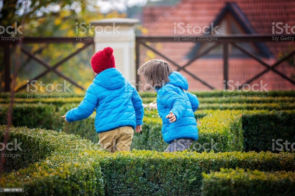 Two children, boys, running happily in labyrinth in the park stock photo