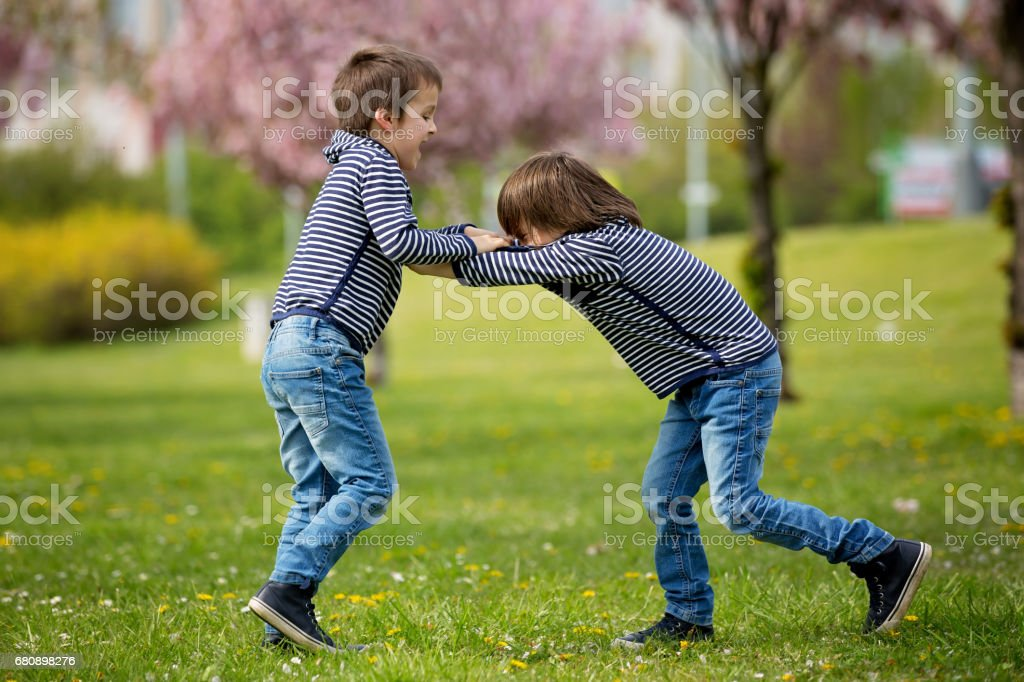 Two children, brothers, fighting in a park, springtime royalty-free stock photo
