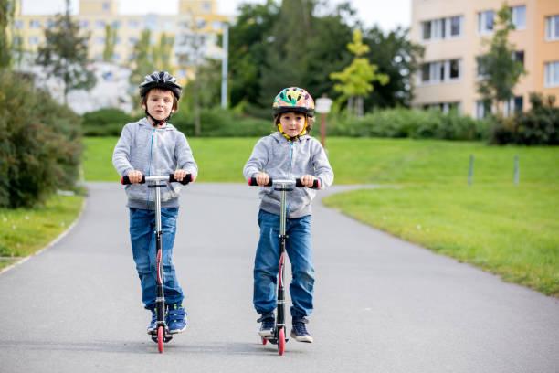 Dos niños, hermanos, montando motos en el parque en un día soleado de otoño - foto de stock