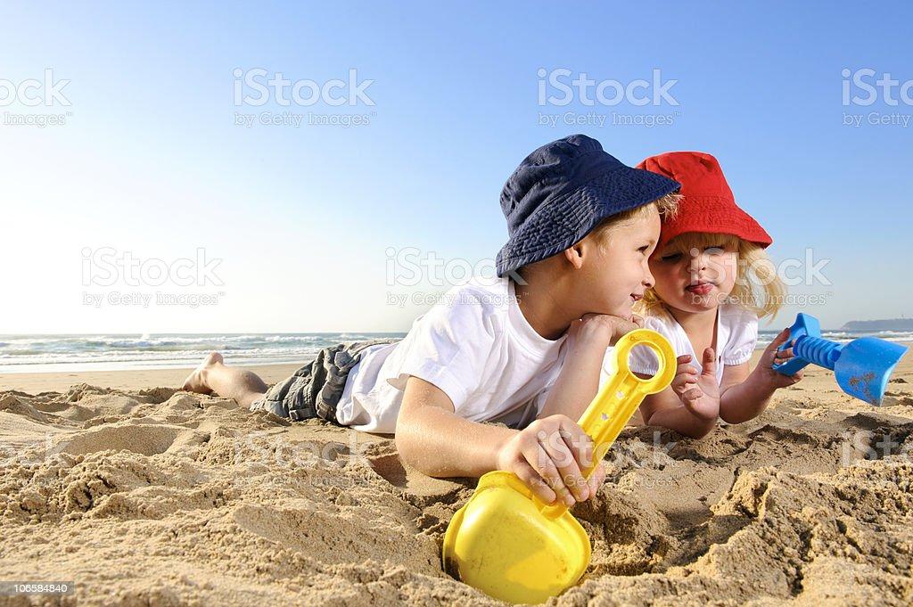 Zwei Kinder Graben in feuchten sand am Strand – Foto