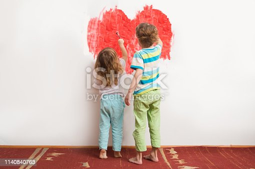 two children draw paints heart on a wall. Happy family day concept