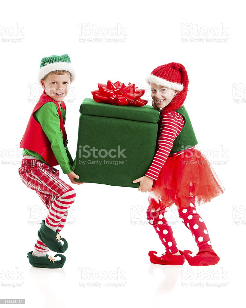 Two children dressed as Christmas elves carrying large gift stock photo