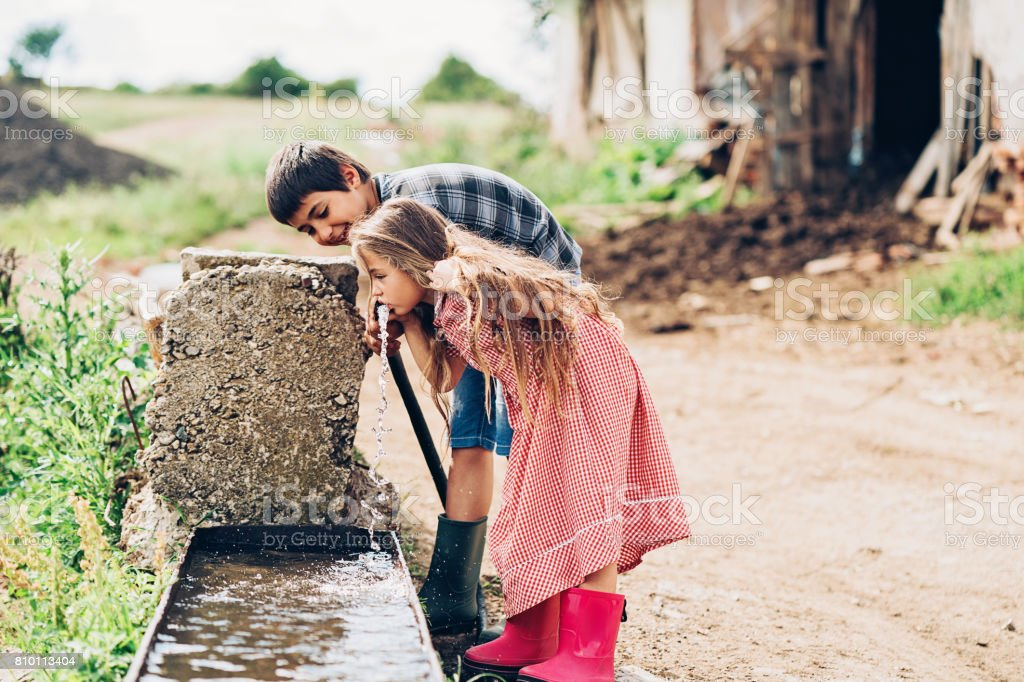 Two children drinking water outdoors stock photo