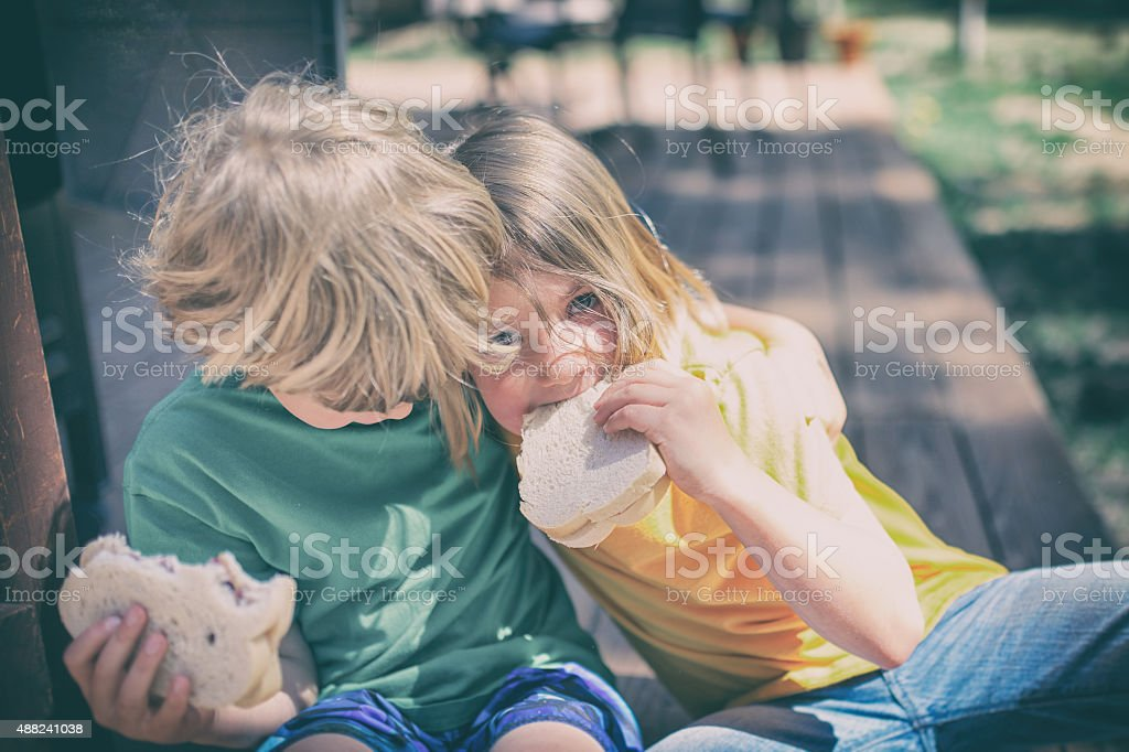 Two children eat lunch on a porch step outside stock photo