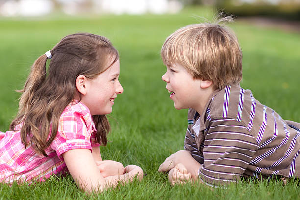 Two children facing each other on grass (Series) stock photo