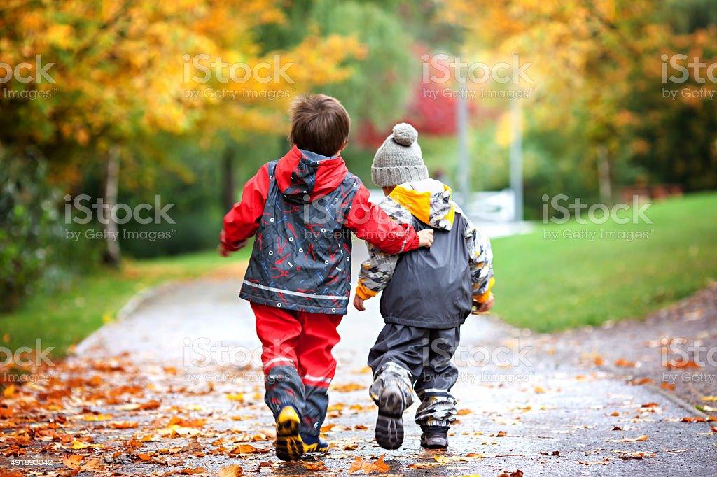 Duas crianças, combate mais de brinquedo no parque em dia de chuva - foto de acervo