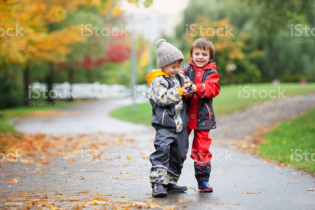 Two children, fighting over toy in park on rainy day stock photo