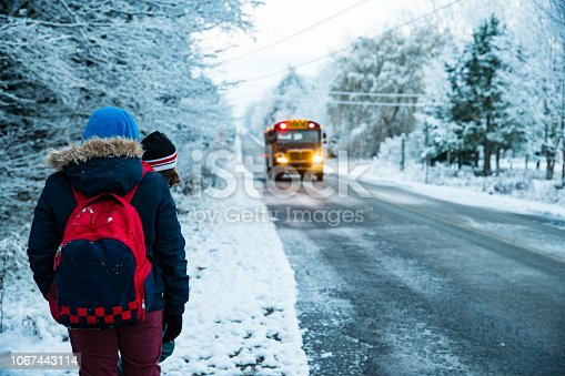 Two children getting on a school bus on a cold, snowy winter morning in the countryside.