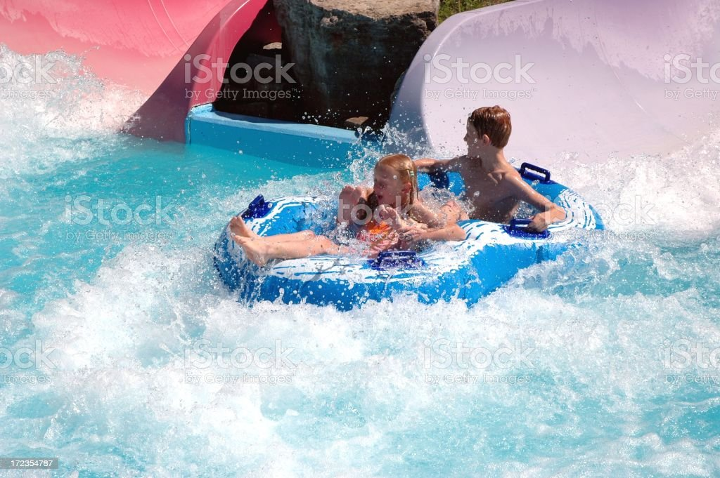 Two children going down a water slide royalty-free stock photo