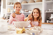 Two children having fun baking in the kitchen, smiling to camera