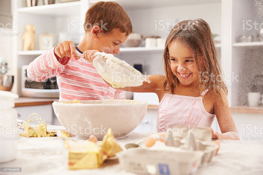 Two children having fun baking in the kitchen stock photo