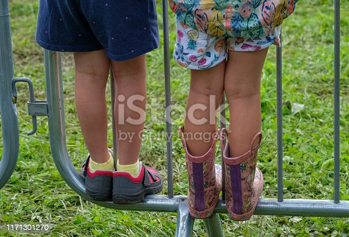View from behind of two children wearing bright clothing, standing on a metal barrier at a sporting event. They have climbed onto the bottom bar to be able to get a better view. The young boy is wearing blue shorts, yellow socks and grey and red sports shoes. The young girl is wearing colourful shorts with a fruit pattern and a colourful jacket and pink and purple rubber boots.