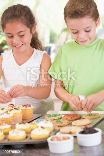 Two children in kitchen decorating cakes and cookies smiling