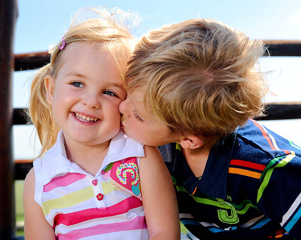 two children in the playground - little girls little boys kissing love stock photos and pictures