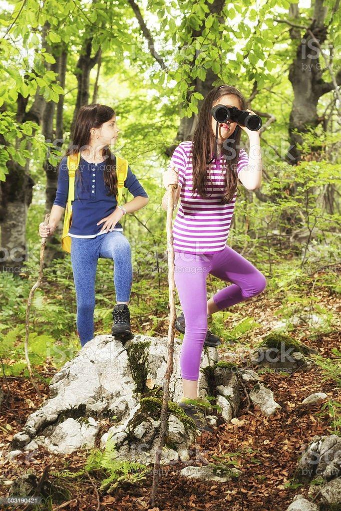 Two children in woods looking through binoculars stock photo