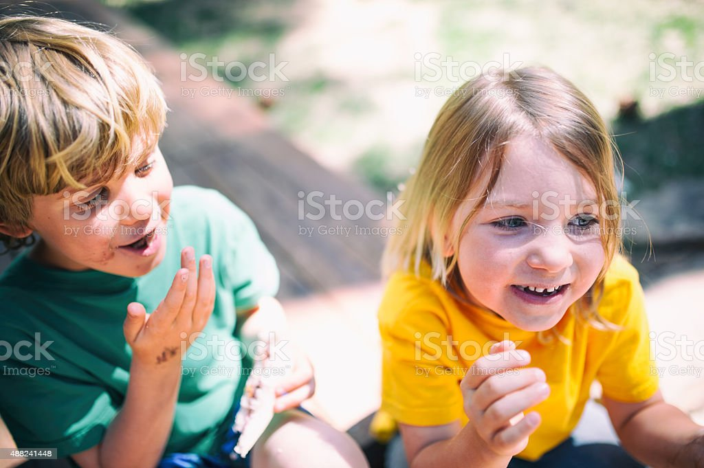 Two children laugh eating lunch stock photo