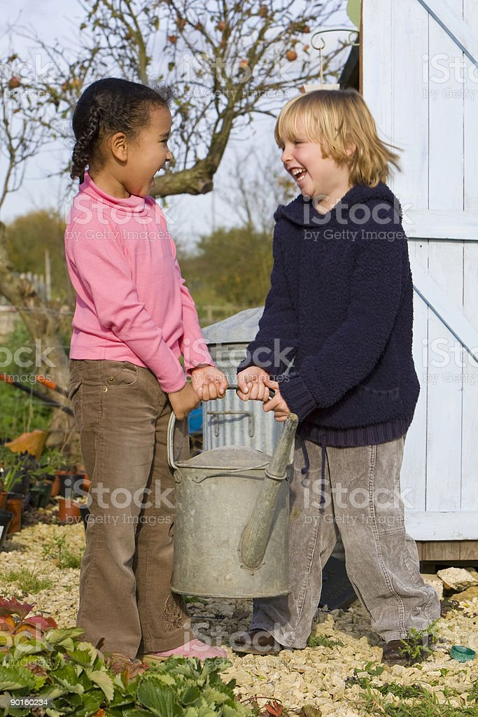 Two Children Laughing Carrying a Watering Can In The Garden royalty-free stock photo