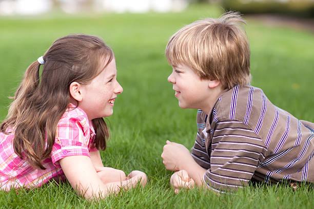 Zwei Kinder lachen zusammen auf Gras (Serie – Foto