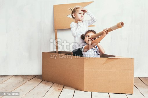 istock Two children little girls home in a cardboard ship play captains and sailors 907621804