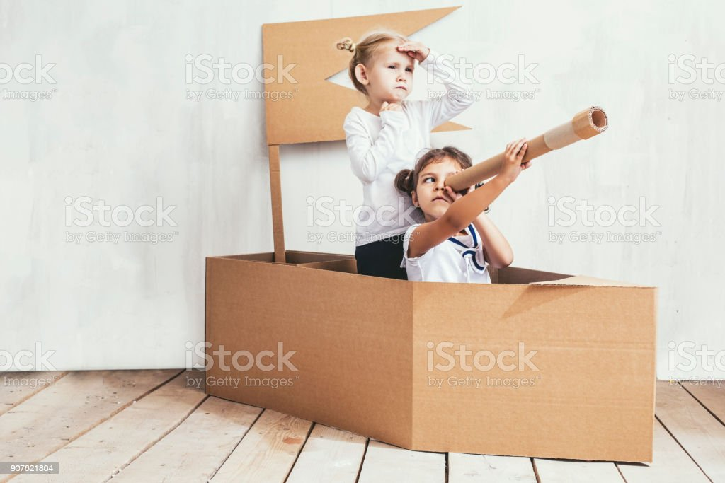 Two children little girls home in a cardboard ship play captains and sailors stock photo