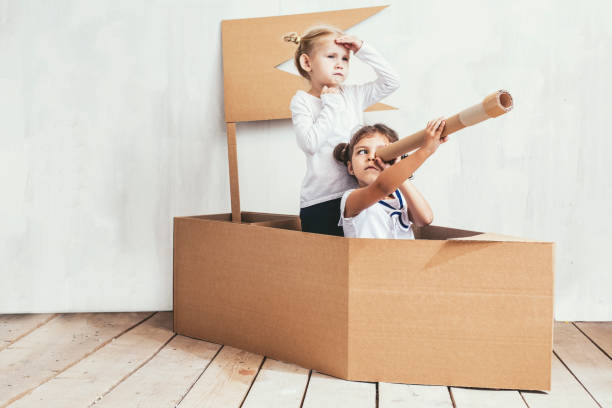 Two children little girls home in a cardboard ship play captains and sailors - foto stock
