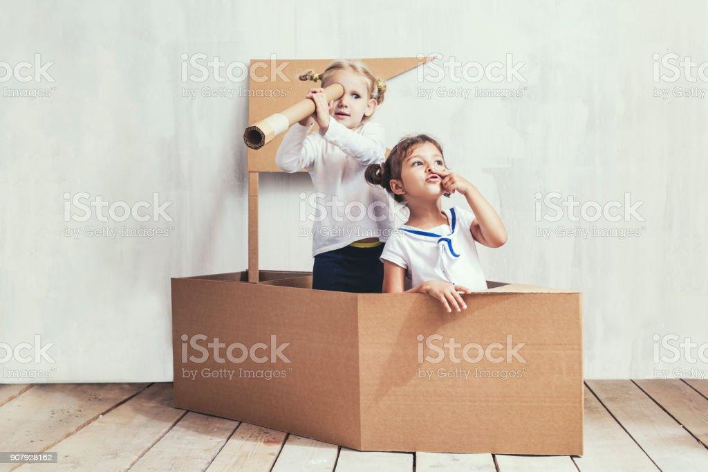 Dos niños niñas en una nave de cartón jugar capitanes y marineros - foto de stock