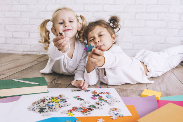 Two children, little girls of preschool age put the puzzle together on the floor stock photo
