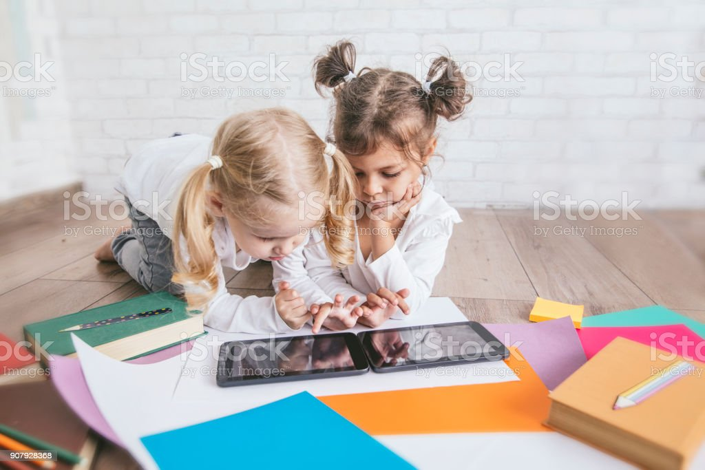 Two children, little girls of preschool age watching tablet at home...