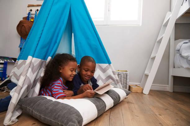 zwei kinder im zelt im spielzimmer mit digital-tablette liegen - tipi bett stock-fotos und bilder