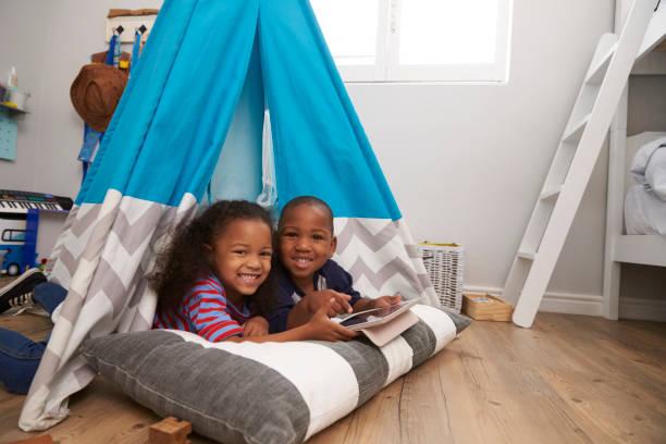 zwei kinder im zelt mit digitales tablet - tipi zelt stock-fotos und bilder