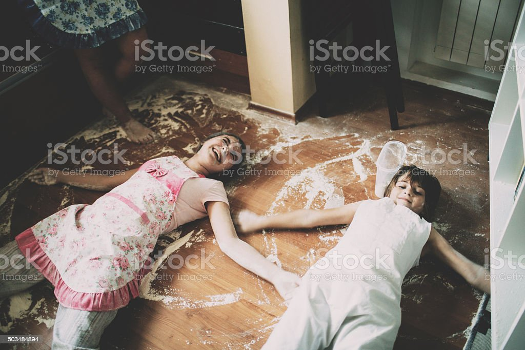 Two children lying on floor in kitchen stock photo