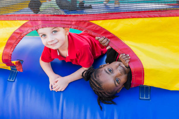 Two children playing in bounce house stock photo