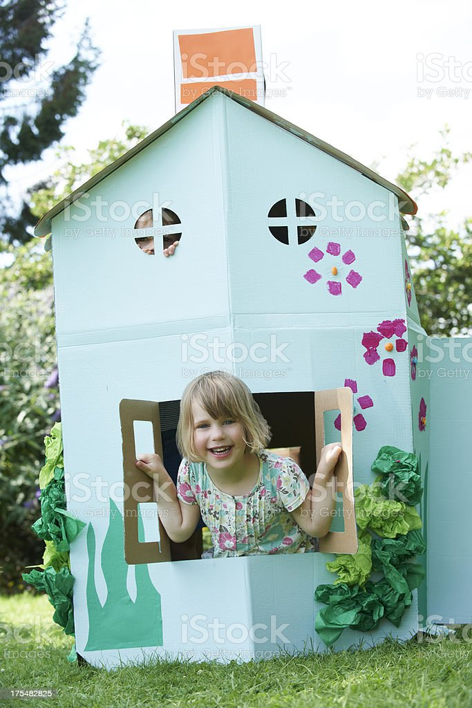 Two Children Playing In Home Made Cardboard House stock photo